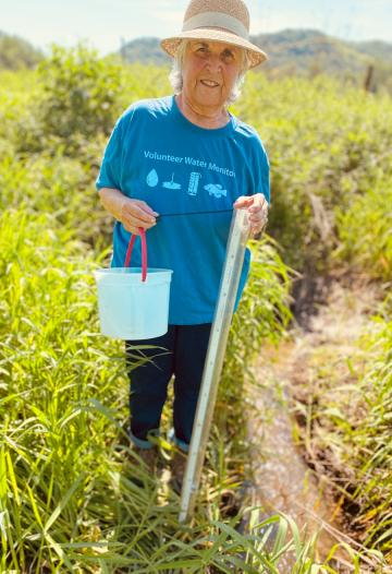 Woman with white hair, a straw hat and blue volunteer water monitor t-shirt stands in tall grass next to a small creek, holding a bucket and clear plastic tube.