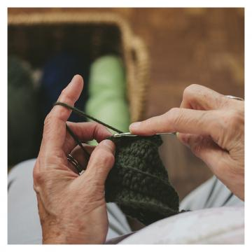 Older person's hands hold dark green yarn and knitting needles with a basket of yarn in the background.