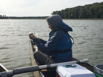 Person in boat on lake gathering water sample in large plastic syringe.