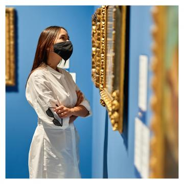 Woman with black face mask looks at picture in a gold frame that is hung on a blue wall with other pictures with gold frames.