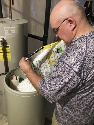 Man filling water softener with salt