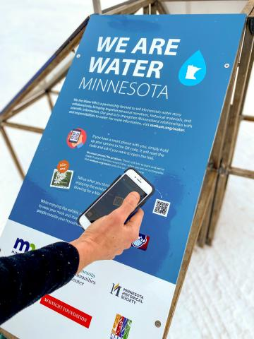 A person scanning a QR code on a sign with a smart phone.