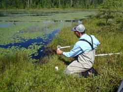 Research Scientist John Genet collects a water sample from a bog pond in St. Louis County. The sampling is part of the MN Wetland Condition Assessment to begin monitoring wetland quality status and trends for all types in the state.